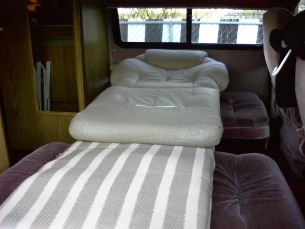 Single Bed Setup in my 1989 Dodge Xtra Class B.  Folded the two back seats down, cut a board to specks to place between the seats then put these cushions in.