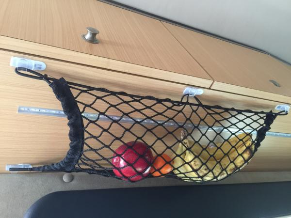 Alvar's Fruit Net on the underside of the galley cabinets held up to 3M Command hooks. The net is from Bass Pro Shops.