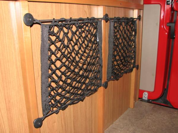 Small nets mounted to outer bathroom wall down low. We keep river shoes and flip-flops in these nets, his and hers. Wet shoes dry out well. Found it at HomeDepot online.