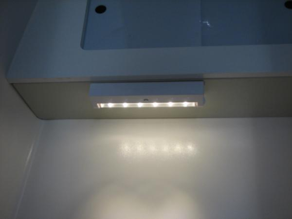 Small under counter battery operated LED light put up with tape. Not very bright especially on low. Keeps you from having to turn on the flood light in the bathroom in the middle of the night. It's also behind you when you...ahem...and thus not in your eyes.