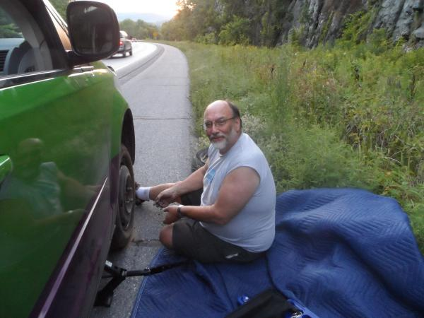 """Changing the tire at the side of the Interstate in Vermont, after waiting two hours.  AAA contractors refused to come - """"too dangerous.""""  Tire """"blew out"""" when the metal valve stem attaching the pressure indicator inside the tire to the rim fatigued and broke.  A minor inconvenience that could have been much worse."""
